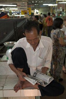 Elderly man reading the paper at a market in Vietnam