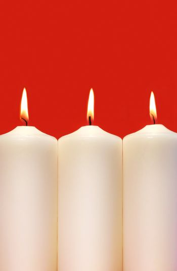 Three white holidays candles on a red background