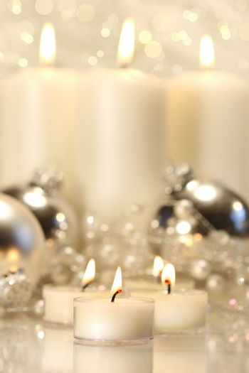 White votive candles with tall candles in background