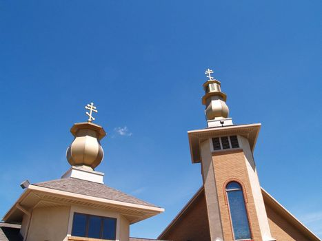 two church steeples with a blue sky in the background