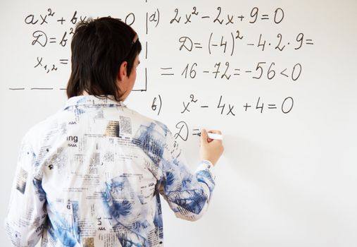 Young teacher teaching algerbra  and writes quadratic equation on a whiteboard