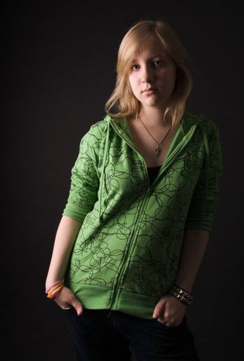 The young girl in green clothes on a black background.