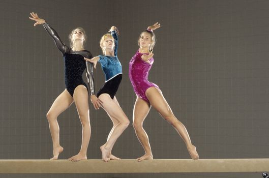 Young gymnasts performing on balance beam