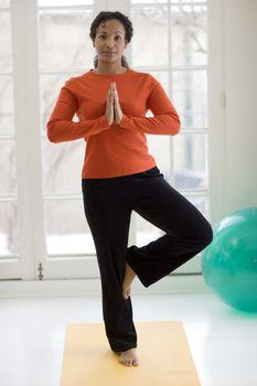 Pretty black woman practicing yoga