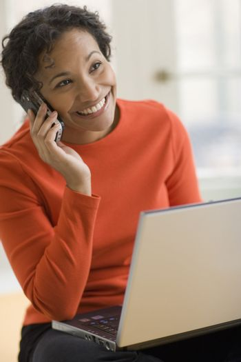 Black woman on cell phone with laptop