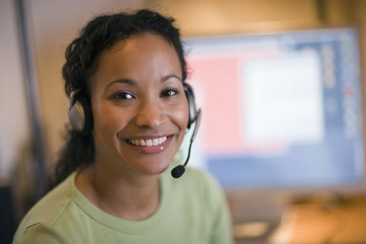 Smiling young African American woman with headset and microphone