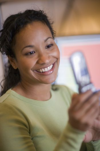 Beautiful black woman texting on cell phone