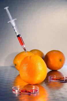 Syringe injecting liquid into an orange