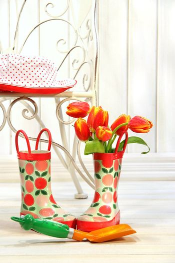 Iron chair with little rain boots and tulips beside