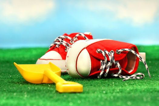 Little red running shoes and shovel on the grass