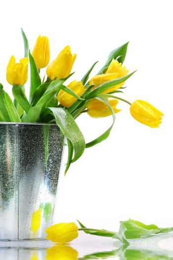Yellow spring tulips on the table with reflection