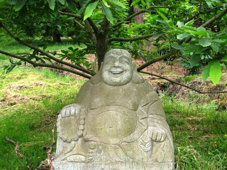 statue of a laughing Buddha under a tree