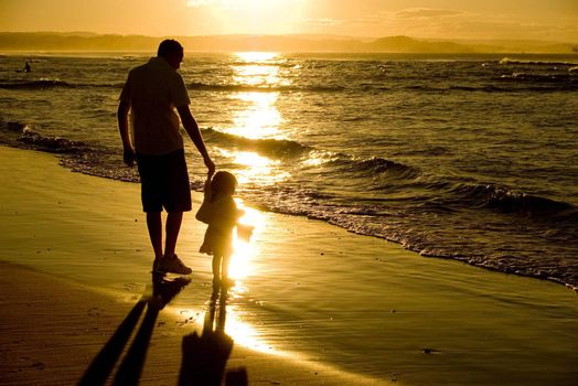 Father and daughter at beach sunset