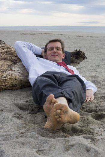 Businessman sleeping on a beach with a smile on his face