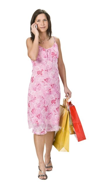 Young woman with shopping bags using a mobile phone.