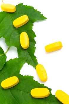 vitamin pills over green leaves