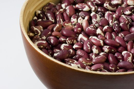 a wooden, round bowl of purple and white anasazi beans, white background, copy space