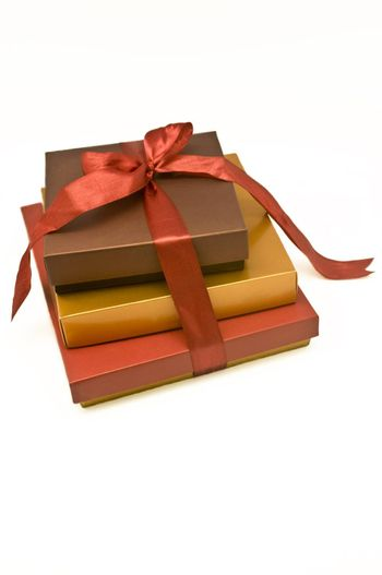 Three boxes tied up with a red satin ribbon.