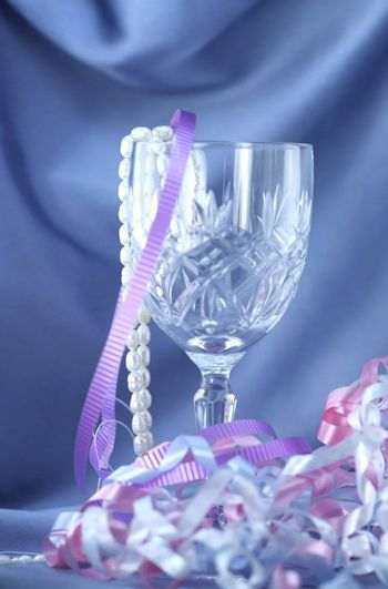 Crystal wine glass and pearls with satin cloth background