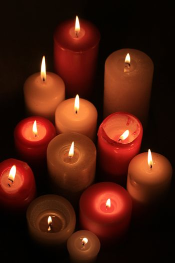 A group of burning candles in red and white