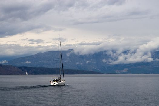 A boat is sailing in a  sea. Stormy clouds on the back
