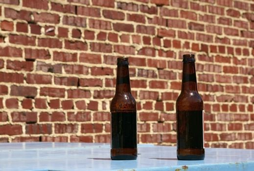Two bottles of beer on a table at an urban bar's outdoor patio.
