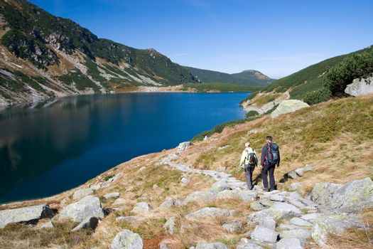 Couple trekking by the side of mountain pond in Tatra Mountains, Poland