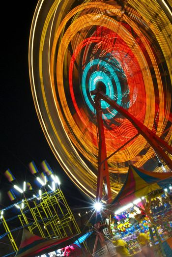 A spinning ferris wheel, colorful flags and carnival games at night