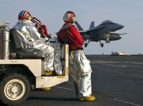 """Sailors assigned to the """"crash crew"""" watch as a Super Hornet lands aboard a nuclear powered aircraft carrier"""