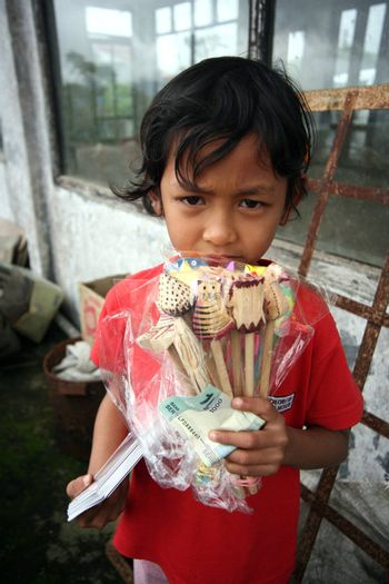 The Indonesian young girl sells souvenirs. Bali