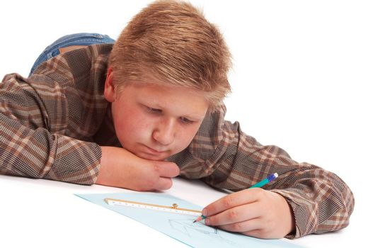 Blond boy drawing a pencil picture lying on the floor; isolated on white
