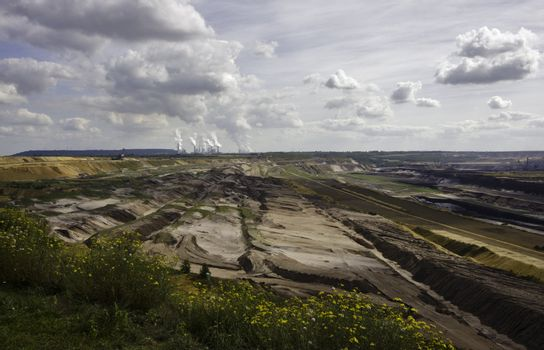 Open-pit mining for lignite (brown coal) that is burnt and tranformed to electricity by the power station at the horizon - largest mining sites and power production site in Germany