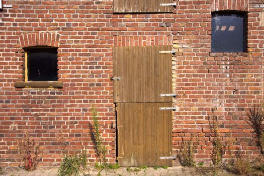 front wall of an old farm building, made of red bricks