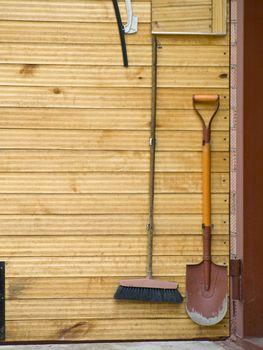Domestic tools shovel and broom at the wooden door