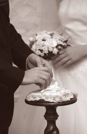 Hands of the groom and the bride during wedding ceremony