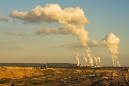 Open-pit mining for lignite (brown coal) that is burnt and tranformed to electricity by the power stations at the horizon - largest mining sites and power production site in Germany