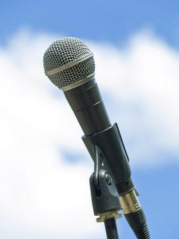 Single microphone against the blue sky with clouds