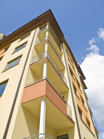 flat building against the blue sky with clouds