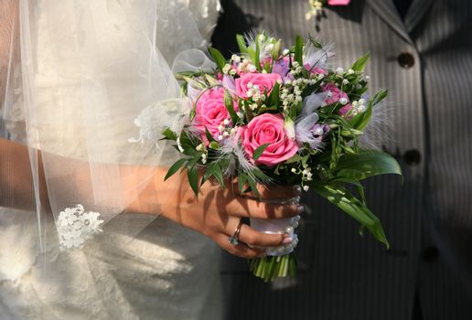 Wedding bouquet in hands of the groom and the bride