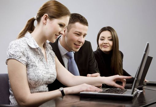 Business group portrait - Young man and two women working together on laptops