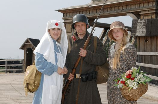 Old style picture with woman in nurse costume, her daughter in flowered dress and man in soldier uniform with weapon. Costumes are authentic to the ones weared in time of  World War I.