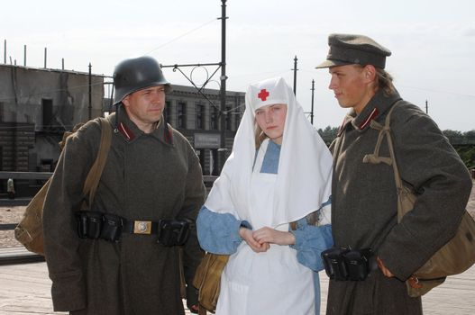 Old style picture with woman in nurse costume and two mans in soldier uniform. Costumes are authentic to the ones weared in time of  World War I.