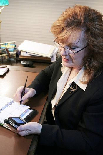 Executive Woman transferring notes from PDA