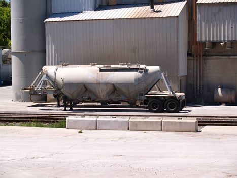 truck sitting by a building at an industrial site