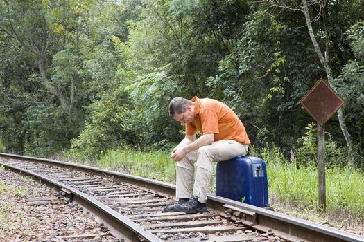 Man sitting on suitcase on railroad tracks