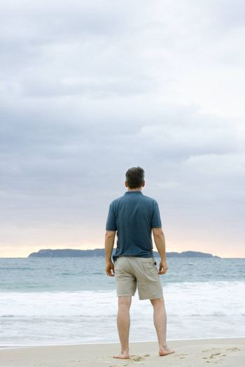 Man standing on the beach contemplating the sea with an island in the background