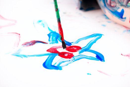 Macro photo of 5 years old boy painting on white background