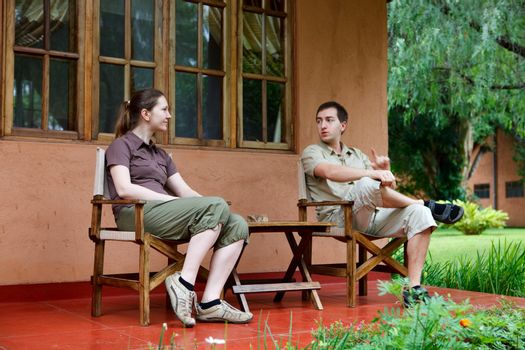 Safari vacation. Young couple in safari clothes sitting in front of their lodge room.