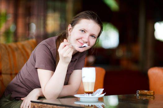 Young beautiful woman drinking latte coffee in safari lodge