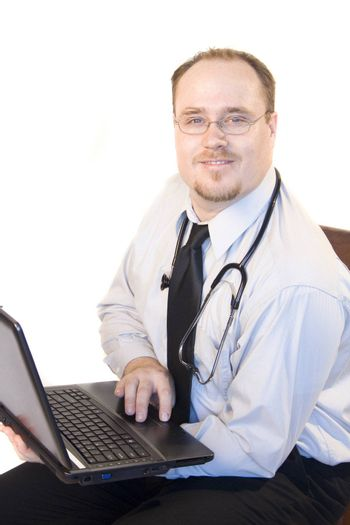 Doctor on laptop smiling isolated on white